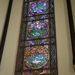 De scheppingsdagen verbeeld in de glas-in-lood ramen achter de preekstoel